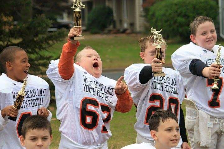 a youth football team celebrates victory. They are all holding trophies.