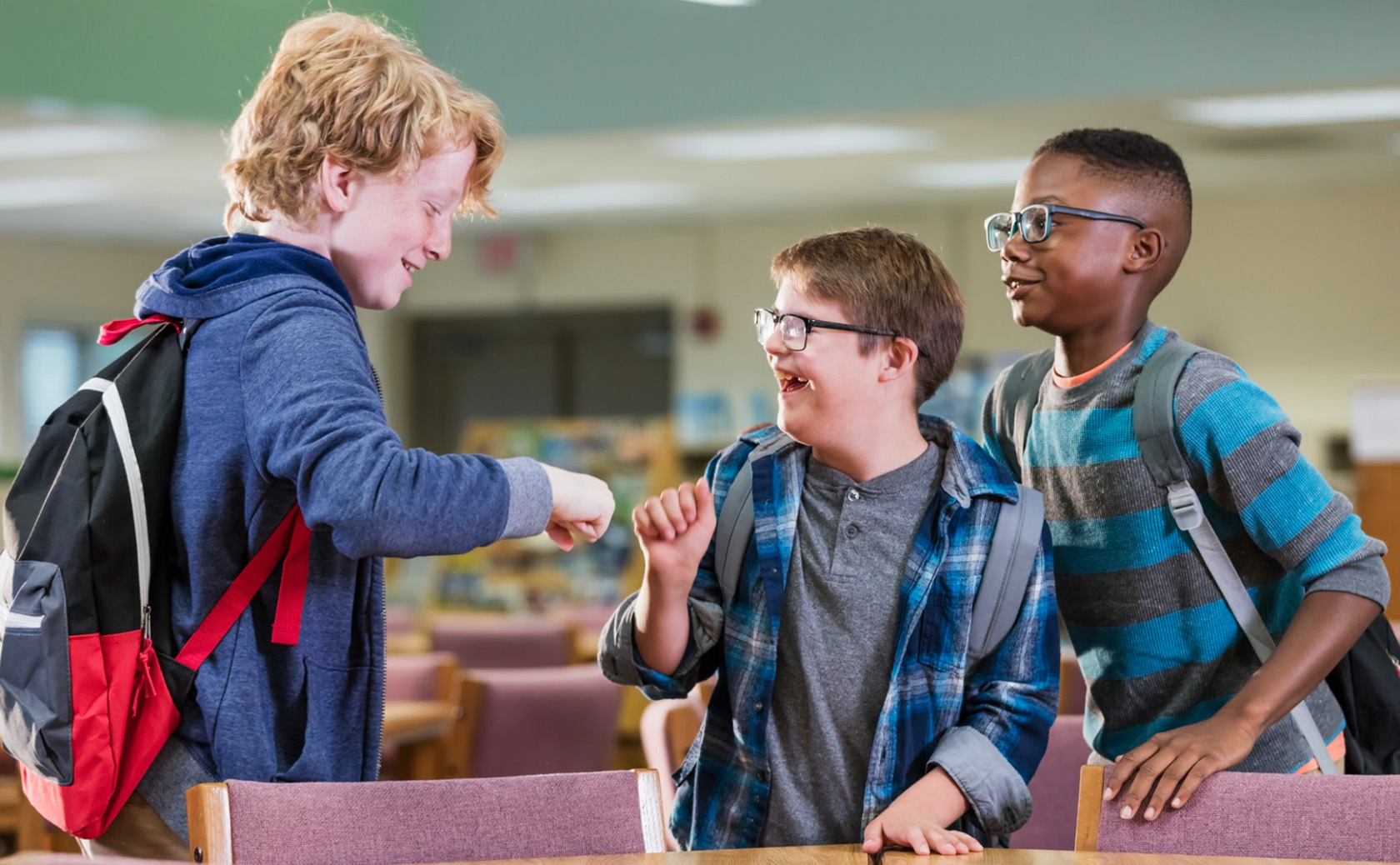 Three male middle-aged students in a cafeteria. Two of the students are fist-bumping. All students are smiling.