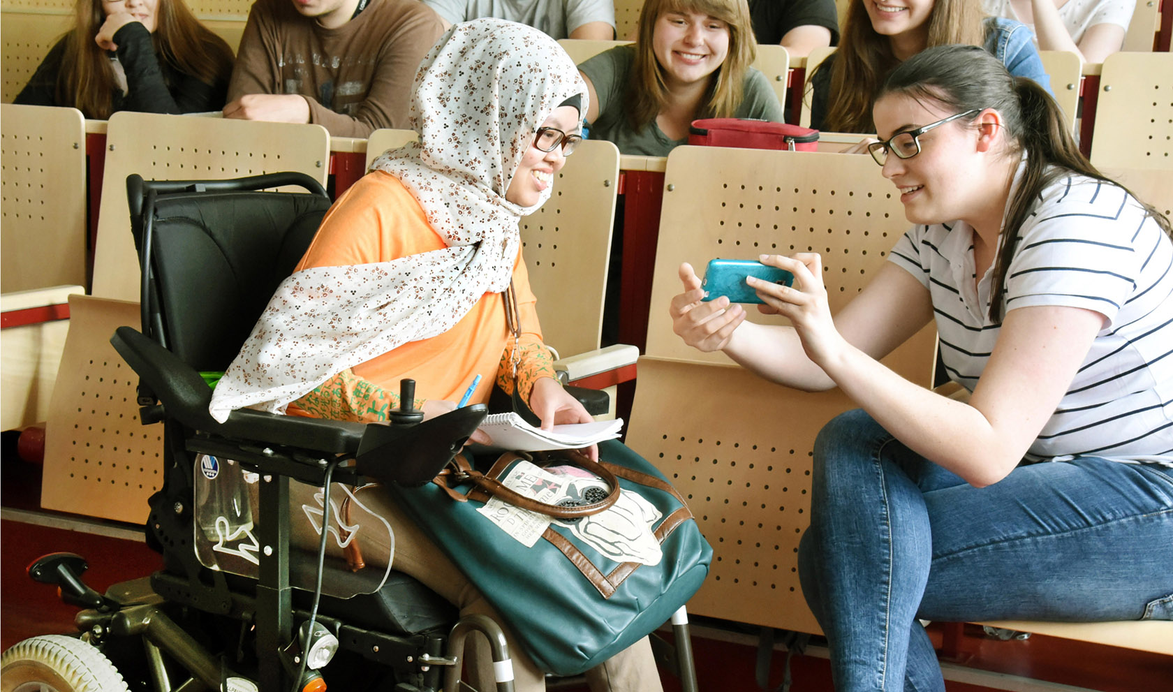 A group of students in an auditorium. One student is showing another student who is in a wheelchair something on her phone. The student in the wheelchair is wearing a hijab.