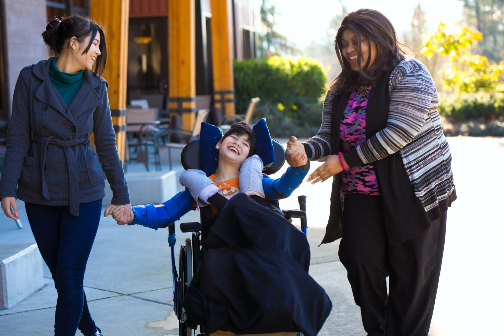 Two adult women and one child are walking together outside near a restaurant. The two women are each holding a hand of the girl, who is using a wheelchair. They are all smiling.